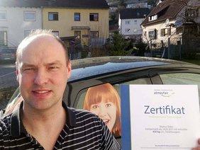 Inhaber Markus Slaby mit CO2-Zertifikat vor Firmenwagen